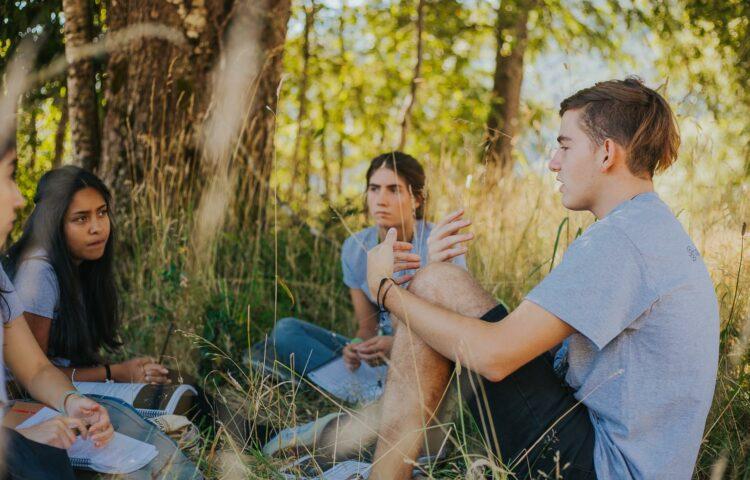 Jóvenes sentados en el pasto