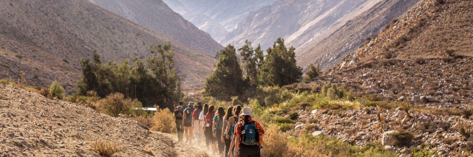 Grupo de personas caminando hacia una montaña