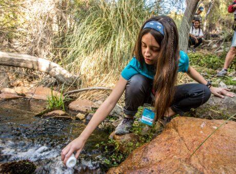 persona tomando agua del rio