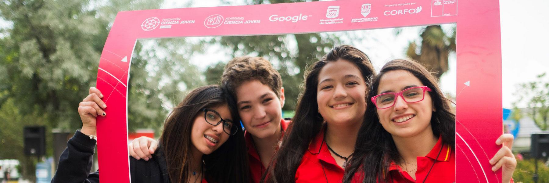 Jóvenes sonriendo sosteniendo cartel